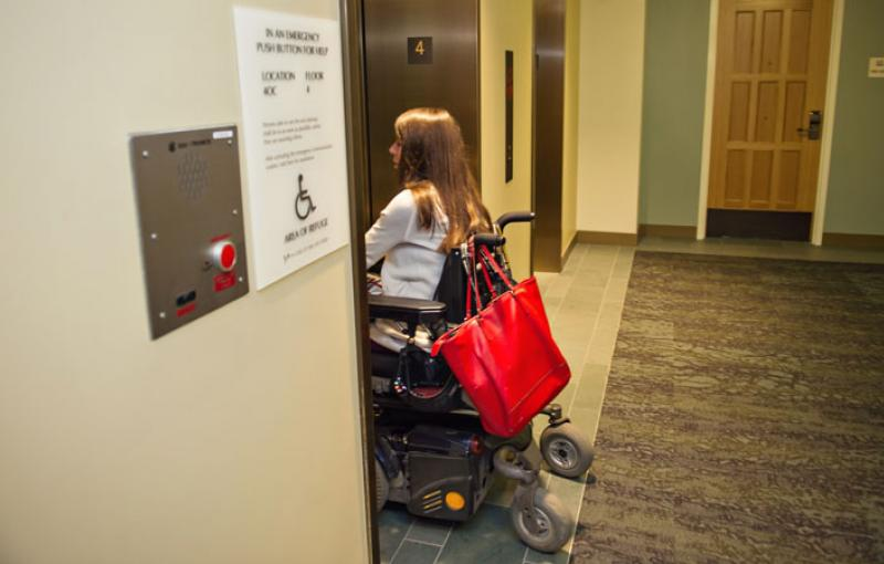 A wheelchair user enters an elevator on campus