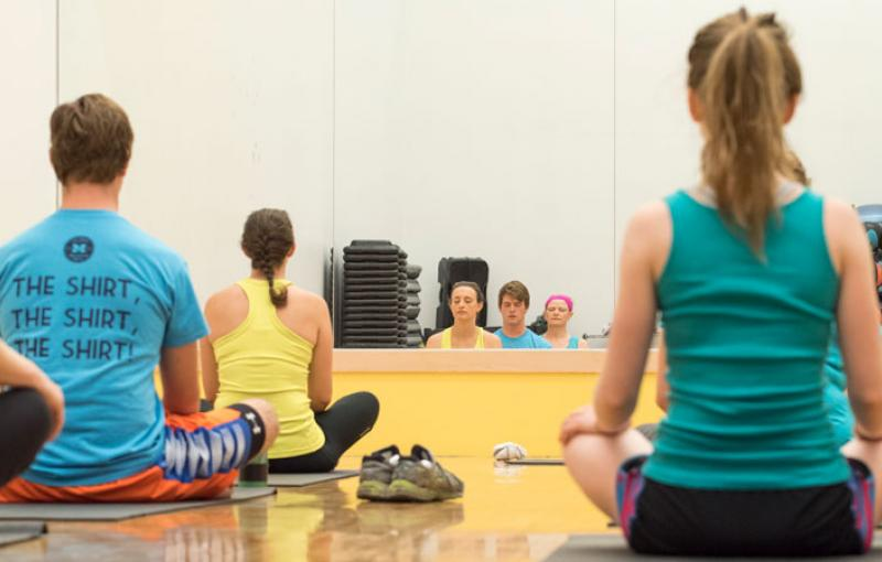 Yoga class participants sit quietly on their mats