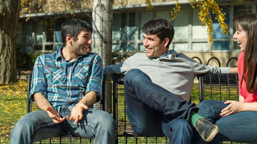 Friends sit on a park bench and talk