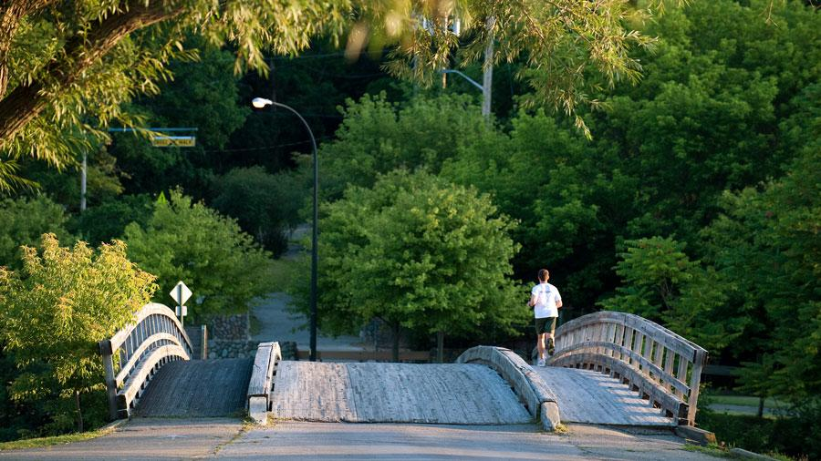 A runner crosses a bridge at Gallup Park in Ann Arbor