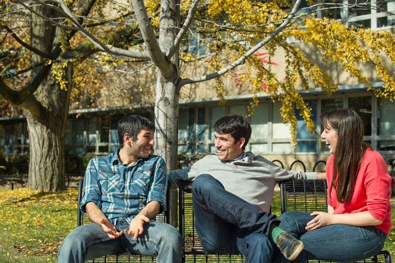 Friends chat on a bench on the medical campus